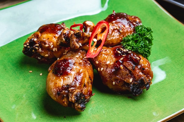 Side view chicken drumsticks fried chicken drumsticks in barbecue sauce wirh sesame seeds and bell pepper on a plate