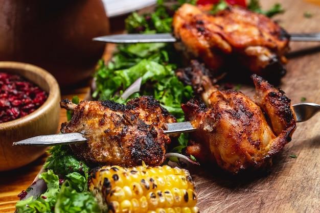 Вид сбоку куриный шашлык с зеленью красного лука, жареная кукуруза и сушеный барбарис на столе