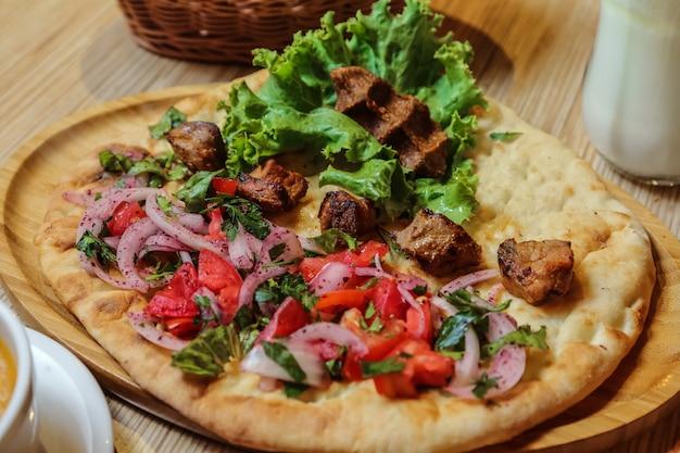 Kebab di pollo vista laterale con pomodoro cipolla ed erbe sul pane tandoor
