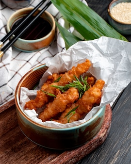 Side view of chicken nuggets with herbs in a bowl on plaid tablecloth