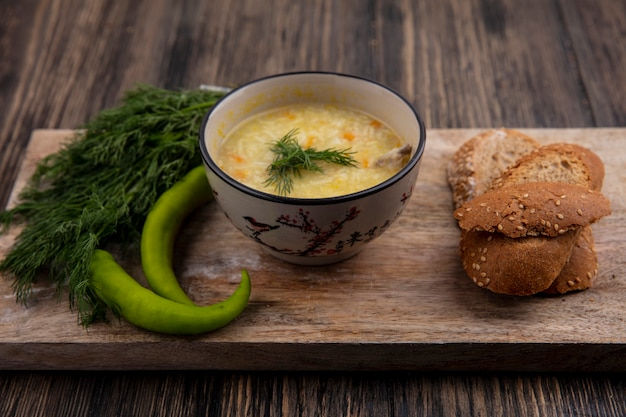 Side view of chicken orzo soup in bowl and seeded brown cob bread slices with dill and pepper on cutting board on wooden background