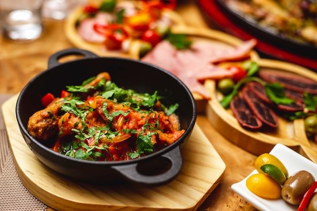 측면보기 치킨 스튜 요리의 일종 테이블에 양파 피망과 채소와 치킨 드럼 스틱 튀김