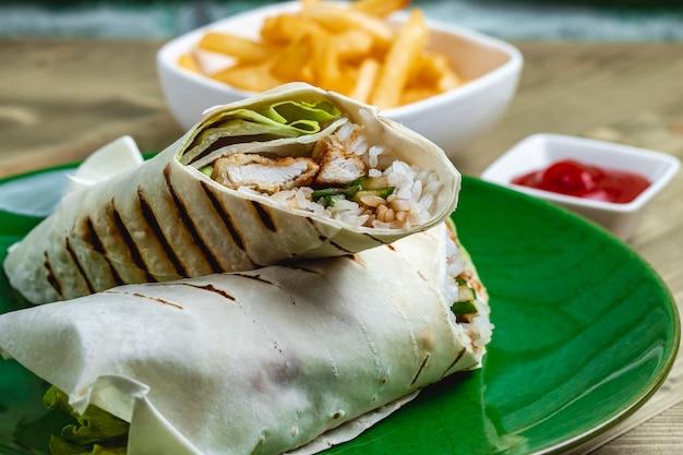 양상추 잎 오이 쌀 치킨 측면보기 치킨 롤 테이블에 케첩과 감자 튀김 스트립