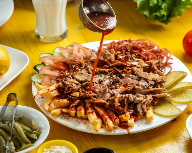 Vista laterale del kebab del doner di chiken sul piatto con i sottaceti e l'insalata della cipolla dei pomodori delle patate fritte del pane