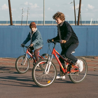 Side view of child friends outdoors on bikes