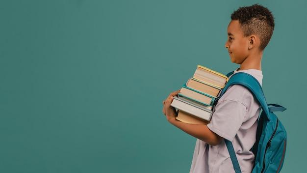Вид сбоку ребенок держит кучу книг копией пространства