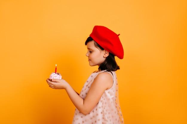 Vista laterale del bambino che tiene la torta con la candela. ragazzo francese festeggia il compleanno.