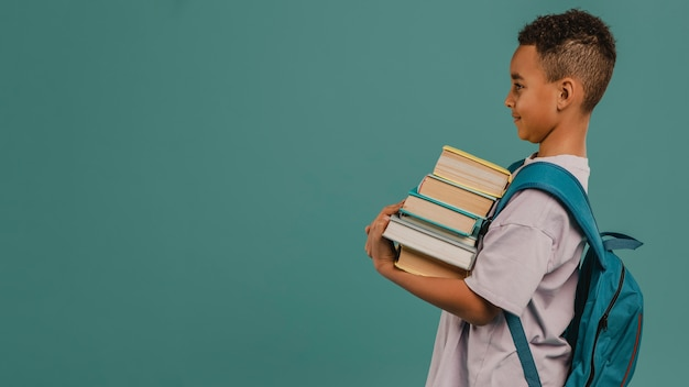 Side view child holding a pile of books copy space