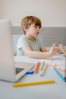 Side view of child at home being tutored with laptop