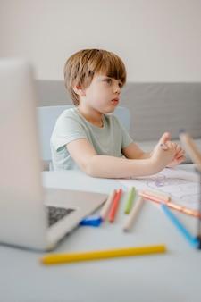 Vista laterale del bambino a casa che è istruito con il computer portatile