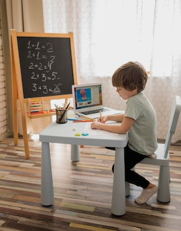 Side view of child at home learning mathematics