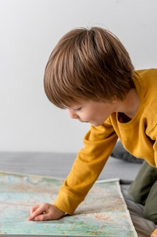Side view of child looking at map at home