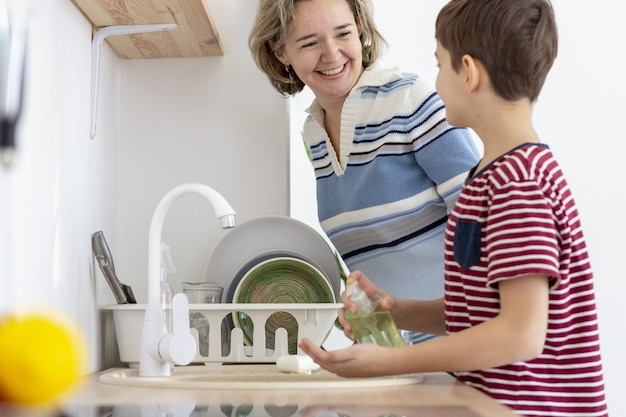 Side view of child washing his hands while talking to his mother