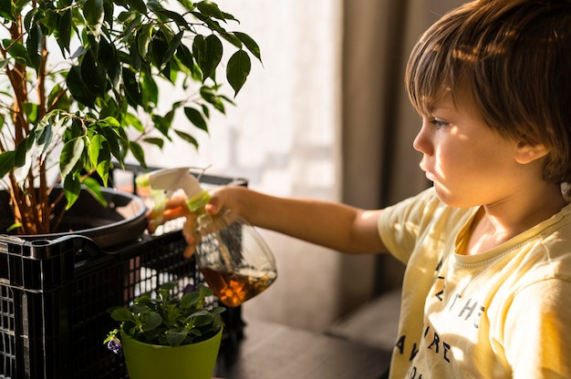 Side view of child watering plants