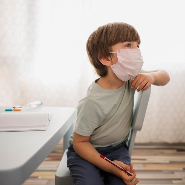 Side view of child with medical mask paying attention to tutor at home
