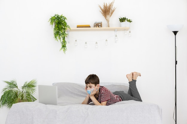 Side view of child with medical mask watching something on laptop in bed