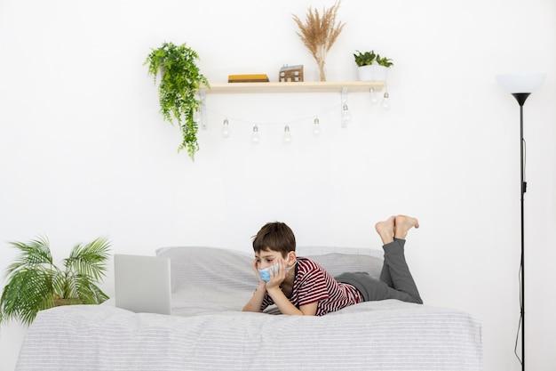 Vista laterale del bambino con la maschera medica che guarda qualcosa sul computer portatile a letto
