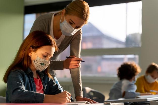 Vista laterale dei bambini che imparano a scuola con l'insegnante durante la pandemia