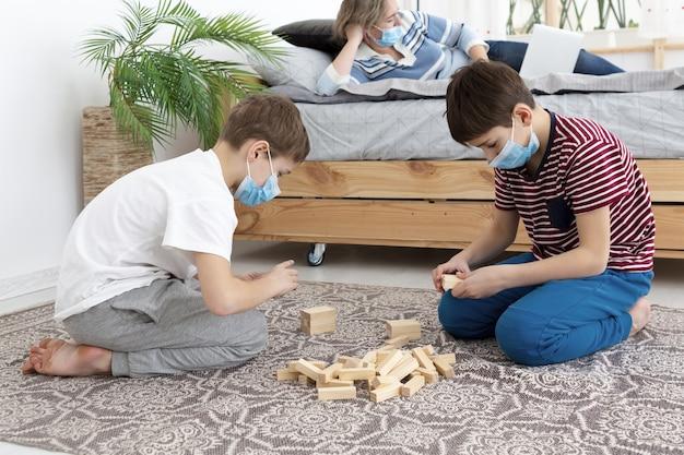 Vista laterale dei bambini con le maschere mediche che giocano jenga a casa