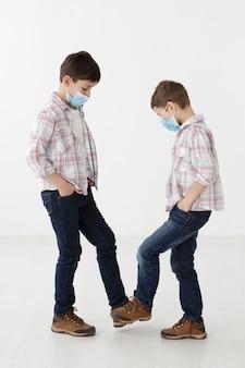 Vista laterale di bambini con maschere mediche che mostrano saluti senza contatto