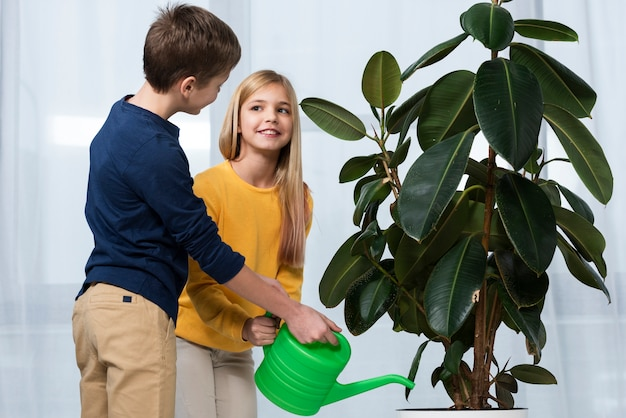 Side view childrens watering flower together