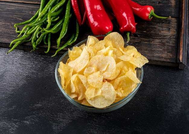 Side view chips in bowl and chilli pepper on cutting board horizontal