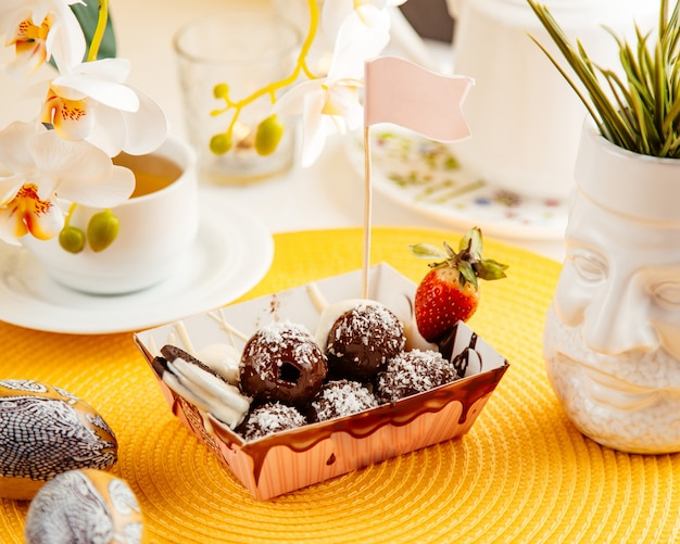 Side view of chocolate balls with coconut sprinkles and strawberry in a cardboard bag