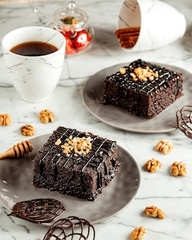 Side view of chocolate brownie cakes on plate served with tea on marble table