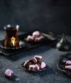 Side view of chocolate candies served with tea on the table