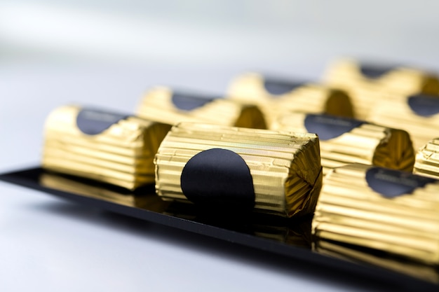Side view chocolate candy in a gold wrapper on black stand