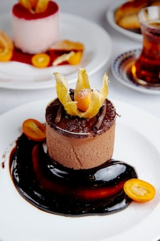 Side view of chocolate cheesecake topped with kumquat
