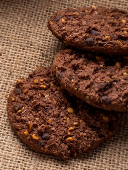 Side view of chocolate chip cookies with cereals nuts and cocoa on sackcloth