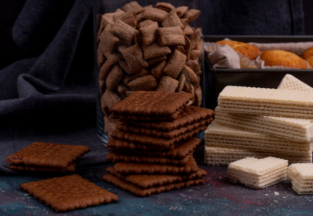 Side view of chocolate cookies and crispy waffles on dark
