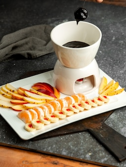 Side view of chocolate fondue with slices of fruits on black