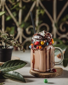 Side view of chocolate milk shake with whipped cream decorated with candies in a glass jar with handle on a wooden stand
