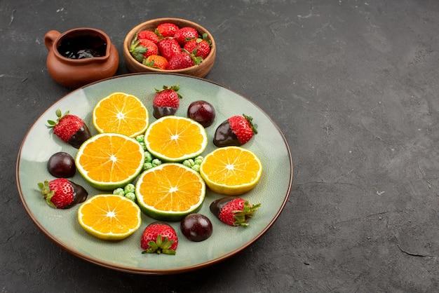 측면 보기 초콜릿 소스와 과일 초콜릿 소스와 딸기는 테이블에 있는 초콜릿으로 덮인 딸기 다진 오렌지 녹색 사탕 옆에 있는 그릇에 있습니다.