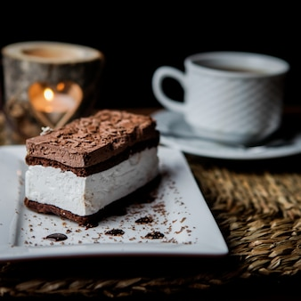 Вид сбоку шоколадное тирамису с чашкой чая и свечой и белой тарелкой в сервировочных салфетках