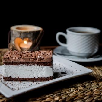 Вид сбоку шоколадное тирамису с чашкой чая и свечой в сервировочных салфетках