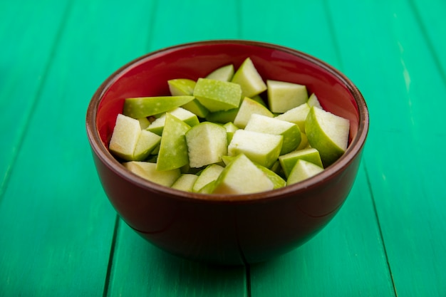 Side view of chopped apples on red bowl on green surface