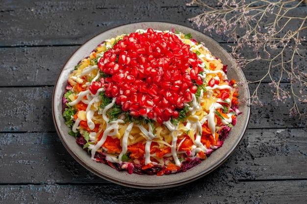 Vista laterale piatto di natale appetitoso piatto di natale con semi di melograno accanto ai rami degli alberi sul tavolo grigio