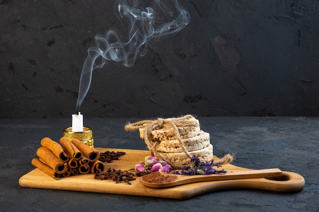 Side view cinnamon with a stewed candle and dried flowers