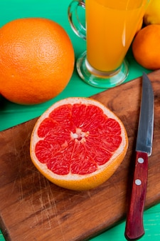 Side view of citrus fruits as grapefruit with knife on cutting board and orange tangerine with orange juice on green background