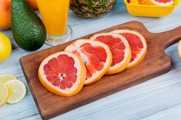 Side view of citrus fruits as lemon avocado pineapple with orange juice and sliced grapefruit on cutting board on wooden background
