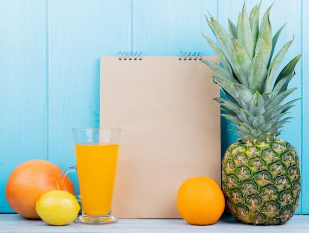 Vista laterale degli agrumi come l'arancia e l'ananas del pompelmo del limone con il blocco note su superficie di legno e fondo blu con lo spazio della copia