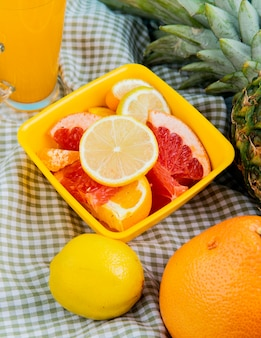 Side view of citrus fruits as lemon tangerine grapefruit kumquat in bowl with orange juice pineapple on plaid cloth background