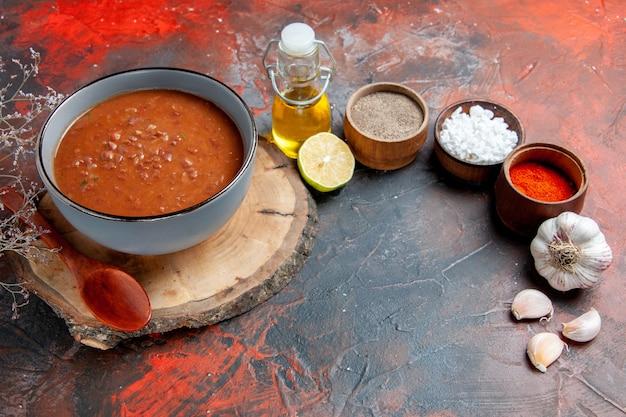 Vista laterale della classica zuppa di pomodoro sul vassoio in legno diverse spezie e olio bottiglia di limone e aglio sulla tabella di colori misti