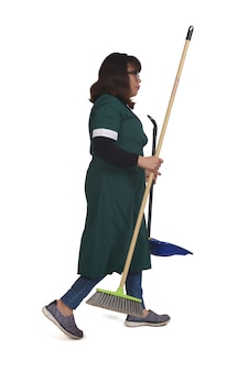 Side view of a cleaning woman with broom and dustpan walking on white