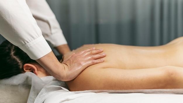 Client di vista laterale alla sessione di massaggio