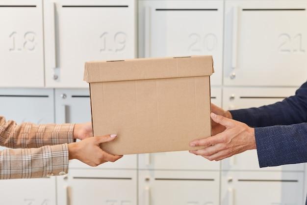セルフストレージユニットまたは郵便箱、コピースペースのそばに立っているときに段ボール箱を手渡している2人で側面図をクローズアップ