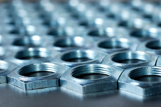 Side view close-up chrome metal nuts in the shape of honeycombs lie next to each other
